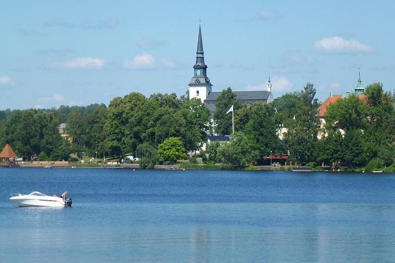 Träd skymmer kyrkan vid sjön i Lindesbergs kommun, där vi jobbar med trädfällning